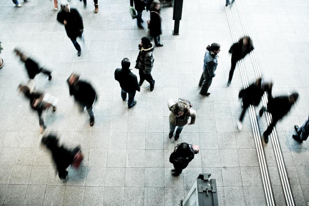 Foto de pessoas se locomovendo em uma estação